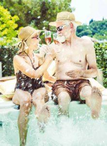 pensionados in Spanje met glas wijn in zwembad