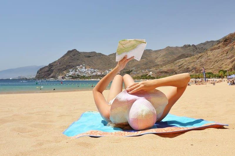vrouw leest boekje op het strand