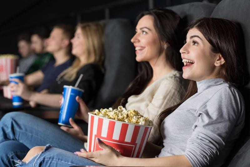Vrouwen eten popcorn in de bioscoop