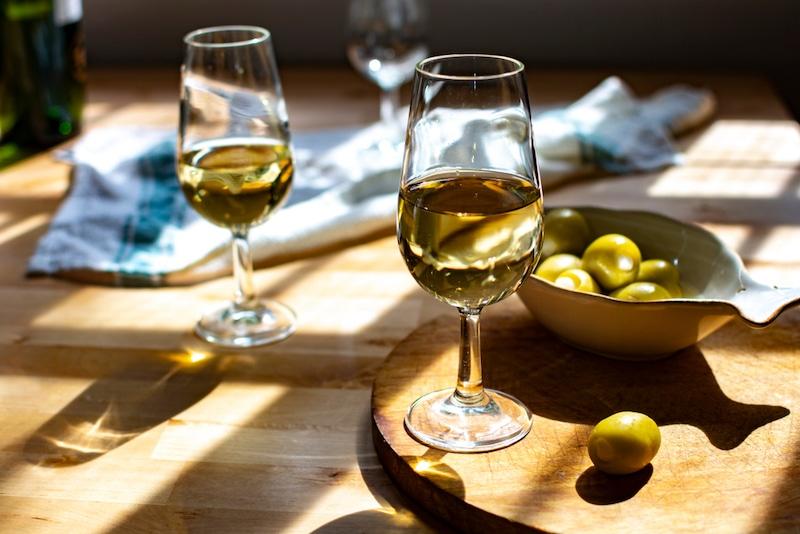 twee champagne glasen met een schaaltje olijven
