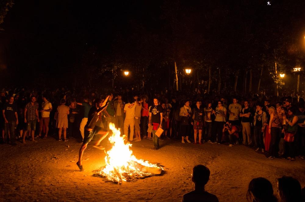San Juan in Madrid mensen om vuur heen en man springt over vuur
