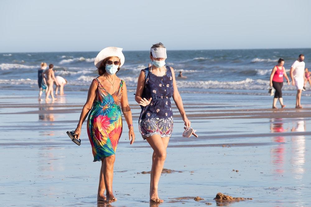 vrouwen langs het strand met mondkapje