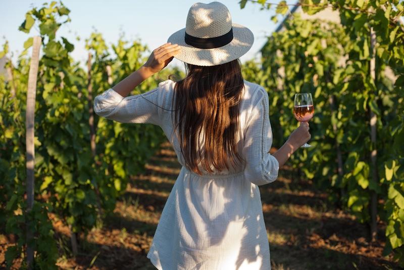 Vrouw met glas wijn in wijnveld