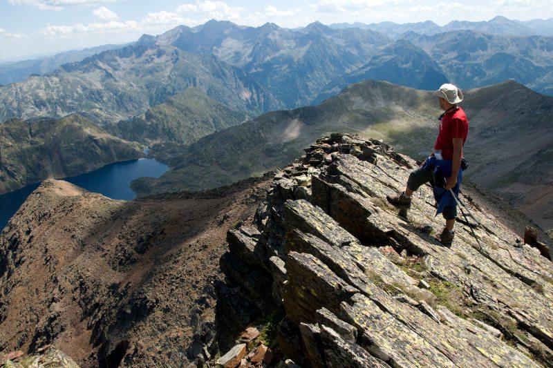 Een wandelaar op de top van een klif in de Pyreneeën