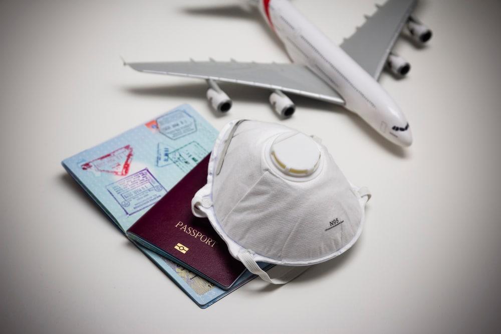 Mondkapje, paspoort en vliegtuig